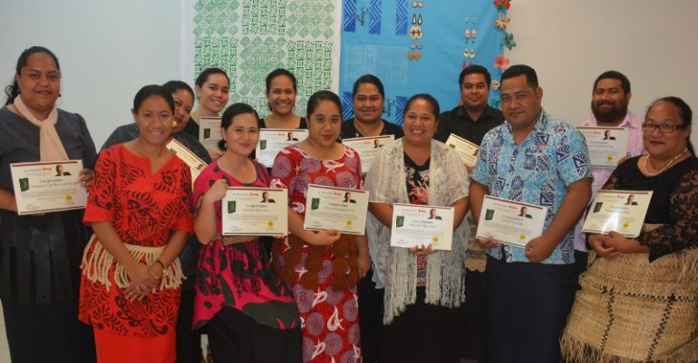 A group of the Maxwell Training Certificate graduates holding their parchments.