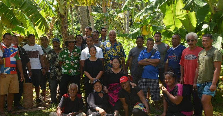 Group of vanilla growers, both male and female, sitting and standing among the trees
